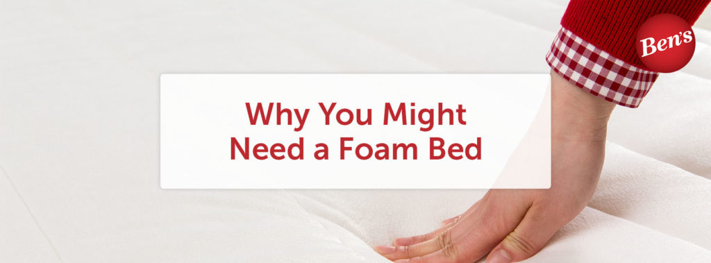 Hand pressing down on a memory foam bed.