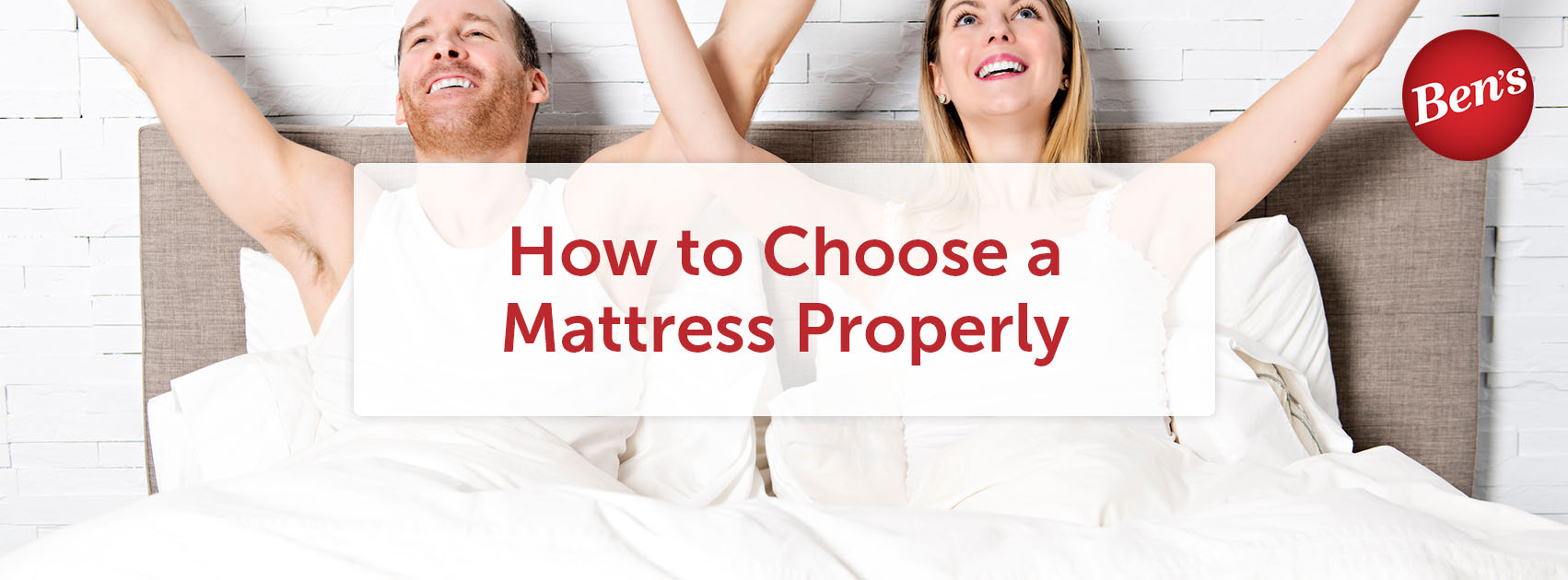 People sitting in bed on a mattress with their hands in the air.